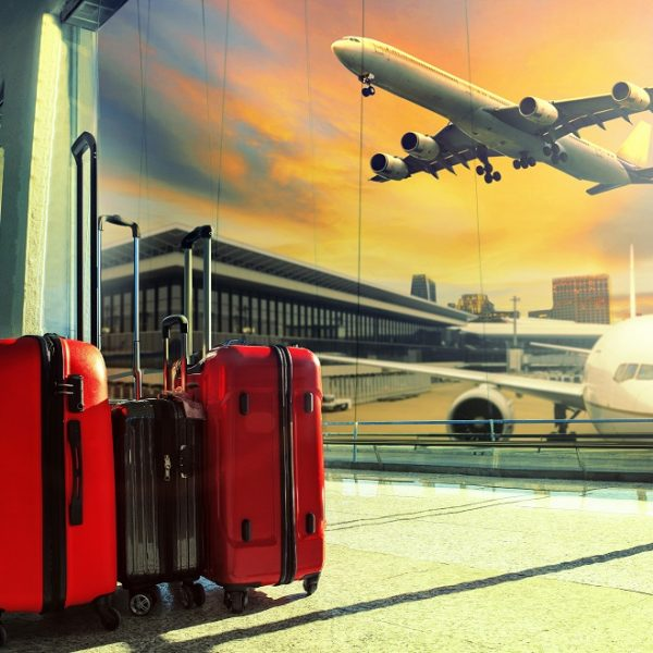 Traveling,Luggage,In,Airport,Terminal,Building,And,Jet,Plane,Flying